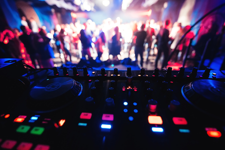 mixer and DJ booth in the nightclub at party c of multi-colored dancers on the dance floor blurred people