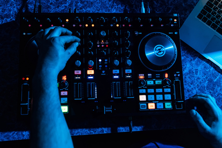 hands of DJ and professional music equipment mixer controlling buttons and levels music
