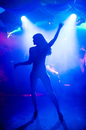 blurred silhouette of a slender young dancer go-go on the nightclub scene under the bright spotlight Stock Photo