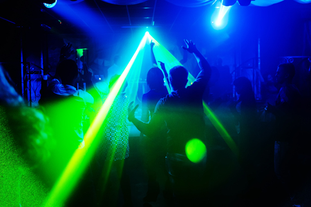 blurred silhouettes of people with their hands up with laser light in nightclub
