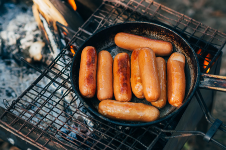sausages fried in a pan on grate of fire on camping Stock Photo