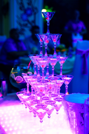 tower of Martini glasses in restaurant with ultraviolet illumination