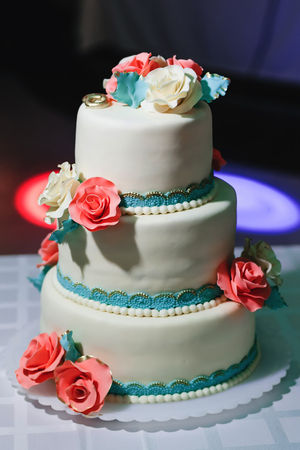 wedding cake with tiers in white glaze decorated with cream flowers