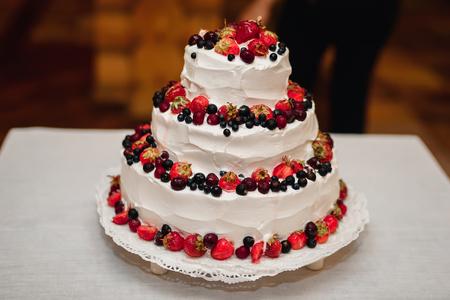 white cream wedding cake with fresh sweet strawberries, cherries, blueberries, black currants Stock Photo