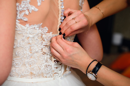 bridesmaid hands fastens buttons on the back of the bride
