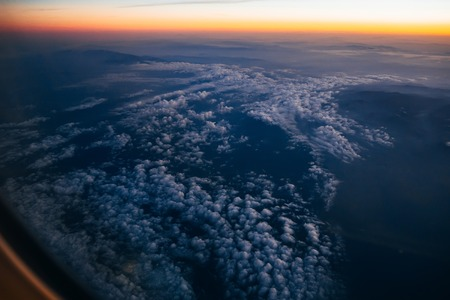View from the window of the plane to the cloudy sky with sunrise Stock Photo