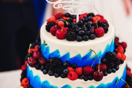 Wedding cake in white blue glaze with fresh berries cherries, blueberries, blackberries, raspberries Stock Photo