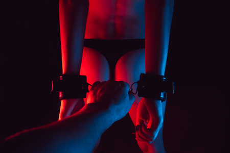 sexy erotic ass of a girl handcuffed with a hand of a man playing role-playing games, for BDSM sex Фото со стока