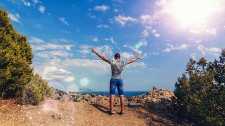 El hombre viajero retrocede en la cima de las montañas con las manos contra el mar y el cielo soleado en verano Foto de archivo