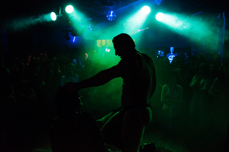 silhouette of a male stripper performing on stage