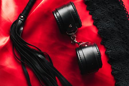 BDSM-Spielzeug für Dominanz und Unterwerfung. Peitsche mit Handschellen