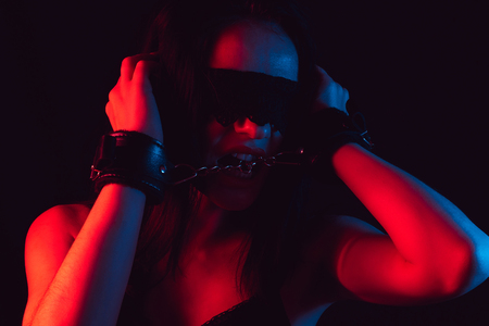 face of sexy girl with lace blindfold and leather BDSM handcuffs Stock Photo
