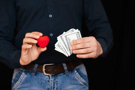 banconote di denaro e un cuore rosso nelle mani di un uomo