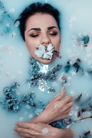 face of a young girl with a flower in her mouth and a bouquet of lilacs relaxing and enjoying in the bath with blue milk and flowers.