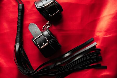 leather handcuffs and black whip for sex games in bdsm sex