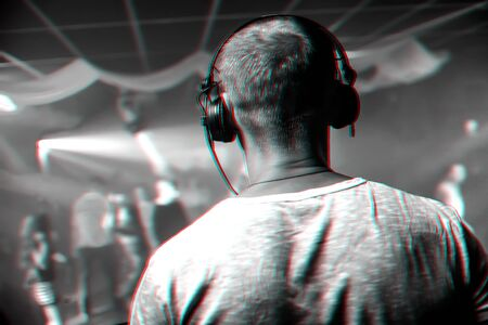 head of a DJ with headphones playing at the event in a nightclub. Black and white photo with glitch effect and small grain