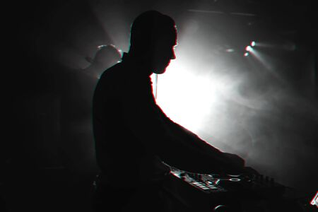 DJ with headphones performs at a music concert in a nightclub. Black and white photo with glitch effect and small grain