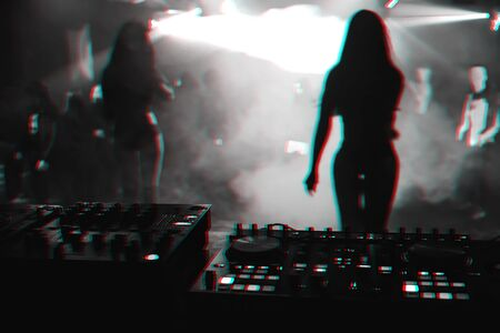silhouette girls dancers on stage in a nightclub on the background music the mixer DJ. Black and white photo with glitch effect and small grain