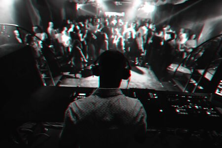 silhouette of a DJ playing music on the mixer and a lot of people dancing in a nightclub on stage. Black and white photo with glitch effect and small grain Reklamní fotografie