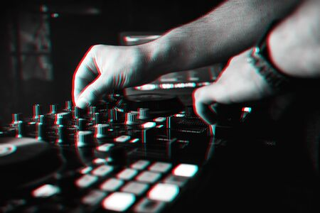 DJ mixes the track in nightclub at party hands driving controllers. Black and white photo with glitch effect and small grain