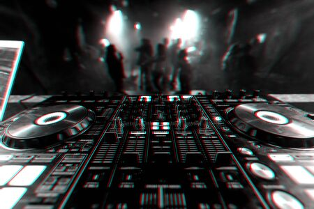 professional DJ mixer controller for mixing music in a nightclub with dancing people on the dance floor. Black and white photo with glitch effect and small grain