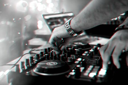 hands DJ mixing and playing music on a professional controller mixer Board in a nightclub at a party. Black and white photo with glitch effect and small grain Reklamní fotografie