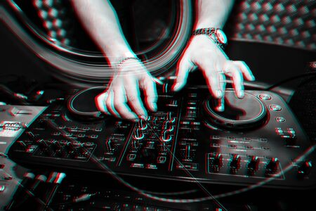 music remote for information and mixing music in a nightclub with a DJ hands close up. Black and white photo with glitch effect and small grain
