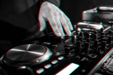hand moving of DJ controllers on music control panel in night club