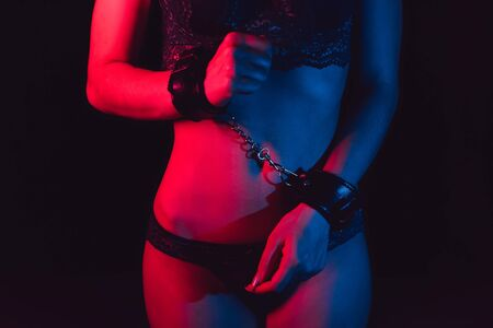 sexy body submissive girl with hands in leather handcuffs in underwear for BDSM sex with submission and domination with neon light Reklamní fotografie