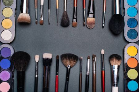 set of brushes and pallets with colored eye shadows