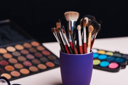 set of makeup brushes on the background of color eye shadow palette
