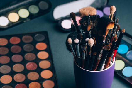 set of professional makeup brushes on a palette background with colored eye shadows