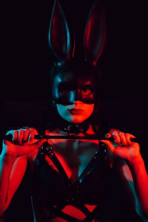 portrait of the girl in the mask Bunny leather belt with a whip