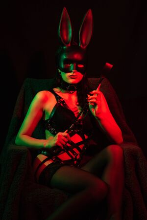 sexy dominatrix woman in erotic lingerie with Bunny mask with leather whip