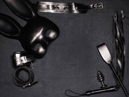set of sex toys on black background. Leather whip, handcuffs, choker, mask and metal anal plug for BDSM sex and role playing Фото со стока