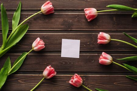 blank greeting card with pink tulips and an empty sticker on a wooden table