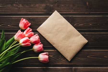 pink flowers tulips with a paper postal envelope on a wooden rustic table Фото со стока