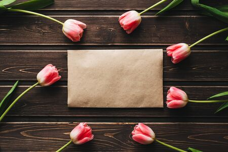 pink flowers tulips with a paper postal envelope on a wooden table