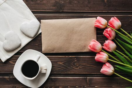 bouquet of pink tulips with a Cup of coffee and white gingerbread in the shape of a heart for the morning Breakfast