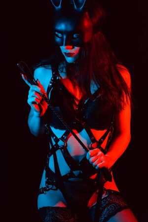 girl sexy lady mistress in a leather belt in the mask of a bunny with a whip
