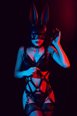 sexy girl dominant mistress in a leather harness and mask Bunny with a whip Фото со стока
