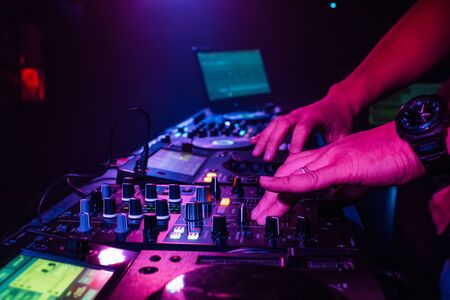 DJ hand mixes on a professional mixer at a party in a nightclub