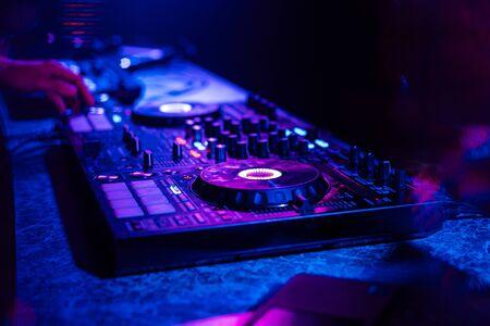 DJ mixer controller at a party in a nightclub by multicolored light spotlights Reklamní fotografie