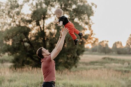dad throws his little son in the field in the summer. Added grain simulates film photo