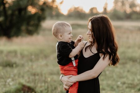 young white mom with son in her arms smiling and happy in summer field. Added grain simulates film