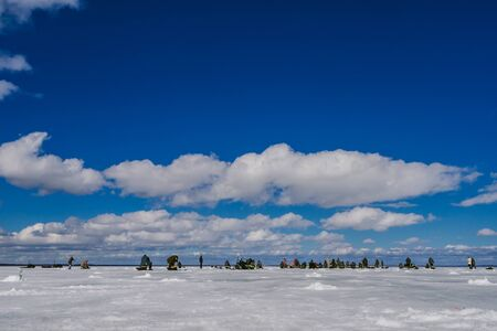 many men fishermen passionate about winter fishing on a frosty Sunny day with a blue cloudy sky on the ice of the river in Russia