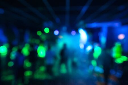 blurred silhouettes of a group of people dancing in a nightclub on the dance floor under colorful spotlights out of focus 免版税图像
