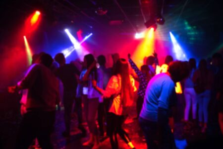 blurred silhouettes of a group of people dancing in a nightclub on the dance floor under colorful spotlights