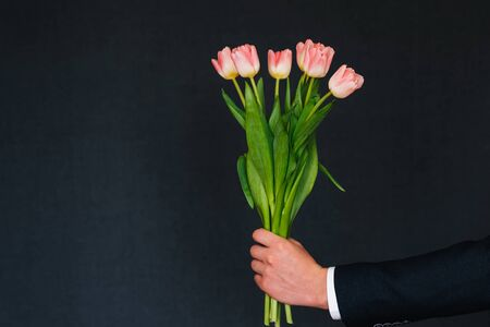 man's hand giving bouquet of pink tulips on blue background with copy space for greeting card