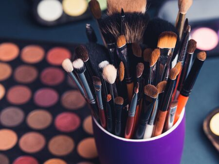 set of makeup brushes on the background of a professional palette with eye shadows